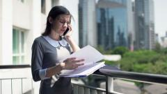 Pretty businesswoman with documents talking on cellphone standing on terrace HD - stock footage