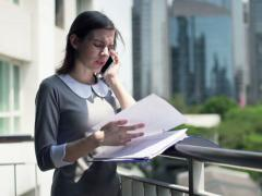 Pretty businesswoman with documents and cellphone standing on terrace NTSC Stock Footage