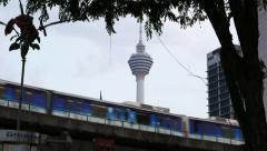 Train drive elevated railroad, against sky and Menara Kuala Lumpur, urban view Stock Footage