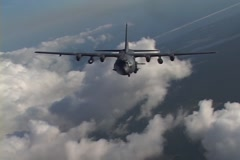 Lockheed AC-130 hercules gunship in flight firing its gun - stock footage