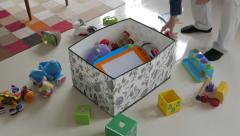 Father puts kid's toys back into toy box Stock Footage