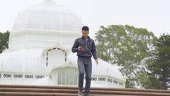 Man Walks Down Stairs Of Conservatory, Toward Camera, Using His Smartphone (4K) Stock Footage