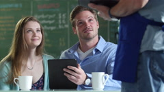 A young couple ordering food in a cafe - stock footage