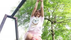 Happy little girl hanging on rings at the playground - stock footage
