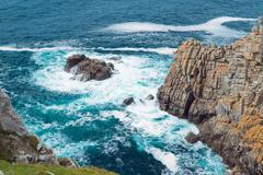 Stock Photo of Rock cliffs on the background of emerald sea. Bretagne, France.