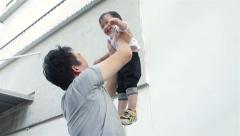 Asian man carry little boy and spin around having fun Stock Footage