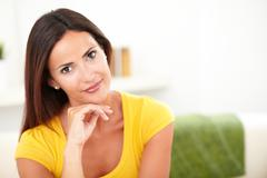 Caucasian woman looking at the camera while contemplating with one hand on he - stock photo