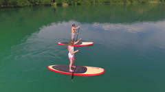 AERIAL: Flying around young couple SUP boarding on a date Stock Footage