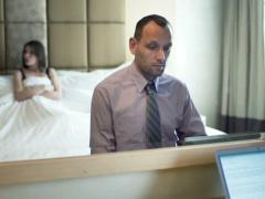 Married couple, businessman working on laptop, unhappy wife lying on bed NTSC Arkistovideo