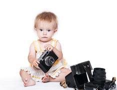 Cute baby girl with retro photo camera - stock photo