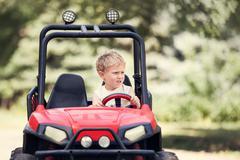 Little boy drive a mini electric car in park Stock Photos