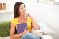 Beautiful woman holding a tablet while sitting with one hand on her chin - in - stock photo