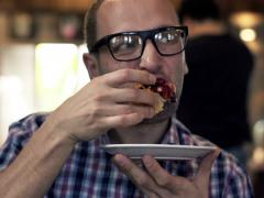 Young man eating tasty, sweet bun in cafe NTSC Stock Footage