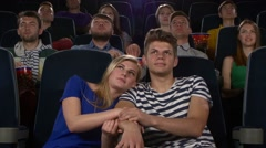 Couple in cinema watching a movie, and kissing Stock Footage