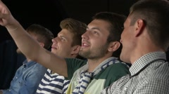 Young people watching movie in cinema. eating popcorn and laughing. Close up Arkistovideo
