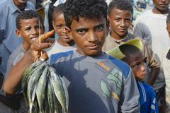 Young fishermen demonstrate catch of the day, Al Hudaydah, Yemen. Stock Photos