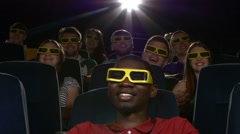 Happy multiethnic young men watching a 3-D movie in the theatre Stock Footage