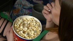 Woman eating large container of popcorn in cinema or movie theater. 3D glasses Stock Footage