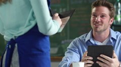 A young man ordering food at a cafe - stock footage
