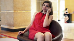 Young woman talking on cellphone while sitting on chair at hotel reception HD Stock Footage