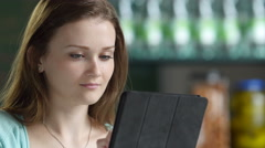 A young woman using an ipad/tablet, close up - stock footage