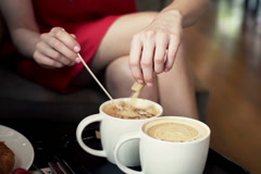 Close up of woman hands adding sugar into coffee in cafe NTSC Stock Footage