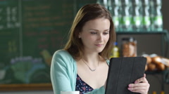 Young woman using an ipad/tablet in a cafe setting - stock footage