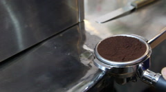 Closeup to barista using tamper into a bucket for making espresso shot, HD Stock Footage