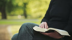 Believer Reading a Bible in a Park - stock footage