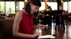 Young woman doing online shopping on tablet computer in cafe  HD Stock Footage