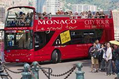 People enjoy sightseeing tour on city tour bus in Monaco. - stock photo