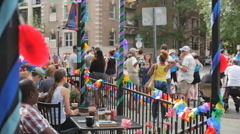 People watch gay pride parade from a restaurant patio with rainbow decorations Stock Footage