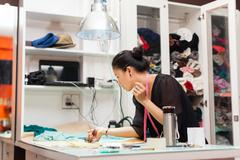 Asian woman tailor fashion clothes dress designer working with fabric Stock Photos
