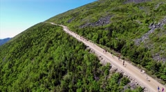 RUNNERS ON MOUNTAIN ROAD AERIEAL Stock Footage
