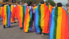 People marching walking in Gay Pride parade with Rainbow flags on backs Stock Footage