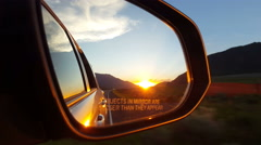 POV - Briliant sunset in mountain pass in auto rearview mirror while driving - stock footage