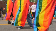 People wear rainbow flags on their backs as they march in gay pride parade Stock Footage