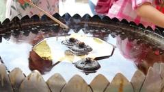 Coconut oil lamp and joss sticks burning at Thai temple ,Bangkok Stock Footage