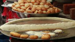 Indian street vendor prepares on the street Indian fried flat bread, Puri. Stock Footage