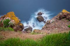 Long exposure image of rocks in wawes - stock photo