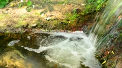 Small waterfall with water falling into a pool with white foam Stock Footage