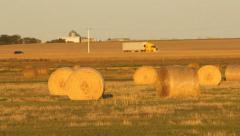 Hay bales in a field. Yellow truck passes in the distance. Saskatchewan, Canada. Stock Footage