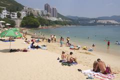 Tourists sunbathe at the Stanley town beach, Hong Kong, China. - stock photo