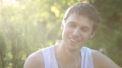 Happy young man smiling at picninc - stock footage