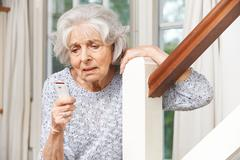 Unwell Senior Woman Using Personal Alarm At Home Stock Photos