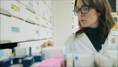 Good looking Pharmacist woman puts a product in the drawer with a prescription Stock Footage