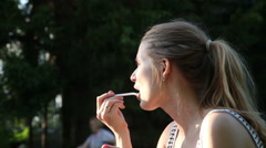 Pretty  woman eating the cake at picninc - stock footage