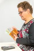 Senior woman counts euro money - stock photo
