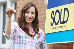Excited Woman Outside New Home Holding Keys - stock photo