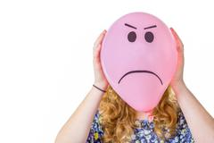 Pink balloon with expression in front  of girls face - stock photo